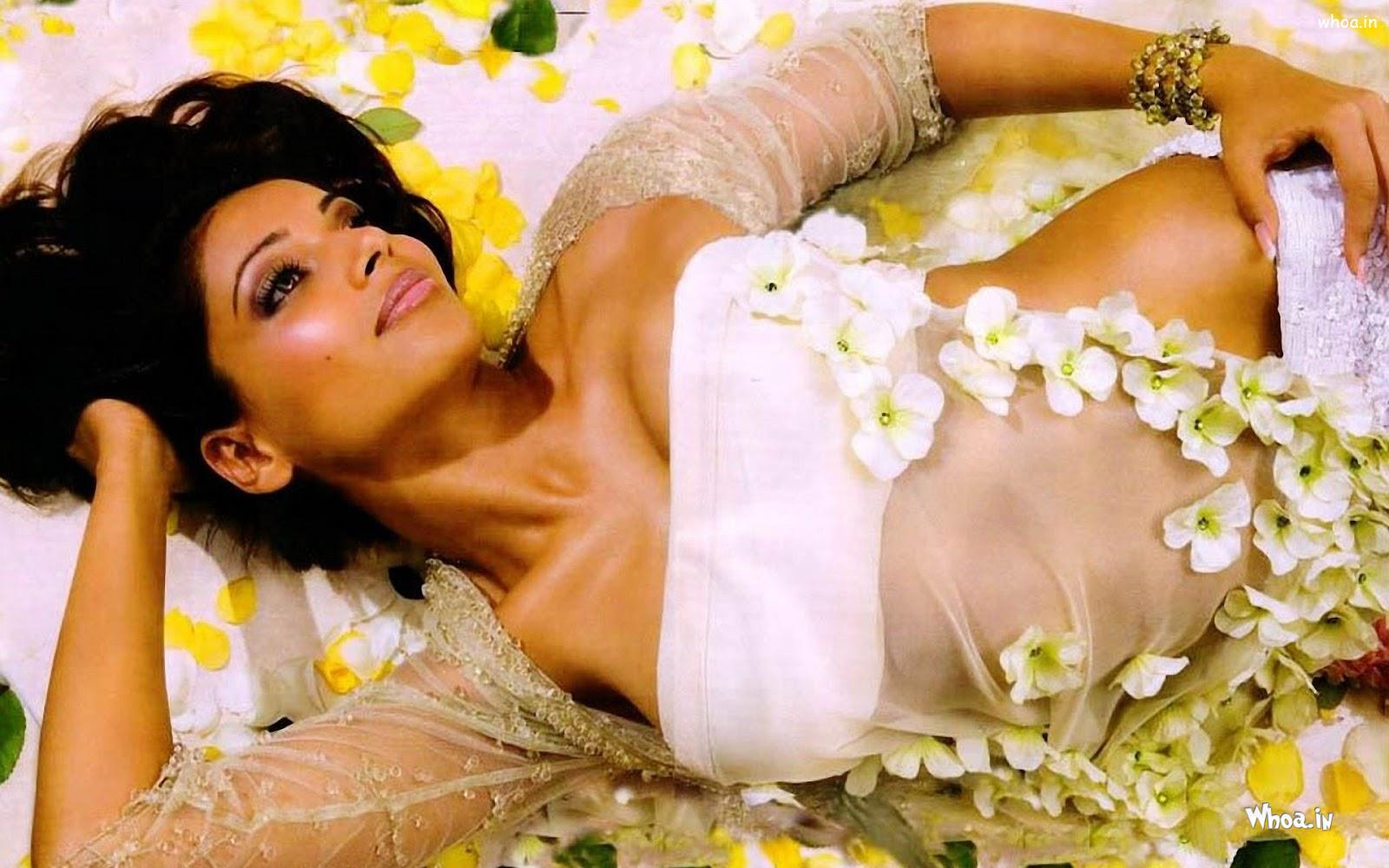 bipasha basu laying on a bed with flowres hot hd wallpaper